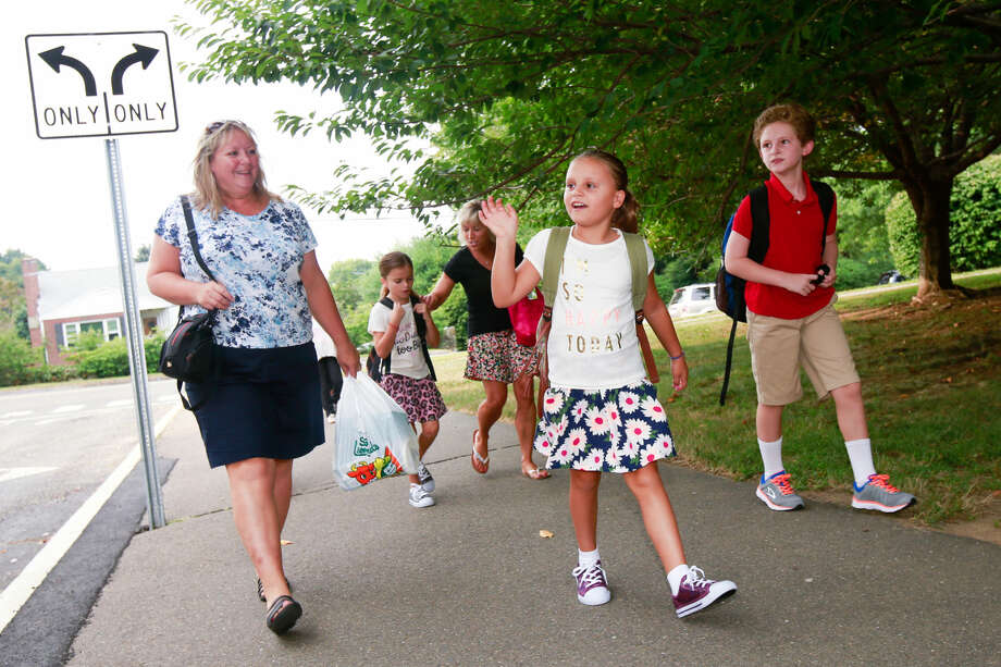 Hour photo/Chris Palermo. Brianna Alfici waves to her friend on the first day of school at Naramake Elementary Monday morning.