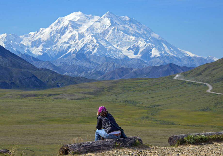 In this Monday, Aug. 3, 2015, photo provided by Holland America Line, a woman gazes at Mount McKinley in Denali National Park and Preserve in Alaska. On Sunday, Aug. 30, 2015, the White House said that President Barack Obama will change the name of North America's highest peak to Denali restoring an Alaska Native name with deep cultural significance. (Andy Newman/Holland America Line via AP)