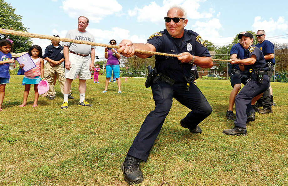 Hour photo / Erik Trautmann Norwalk police officer Mark Kucky pulls for the NPD in a tug-o-war competition during the SoNo Day Out at Ryan Park sponsored The Norwalk Police Department Community Services Division.