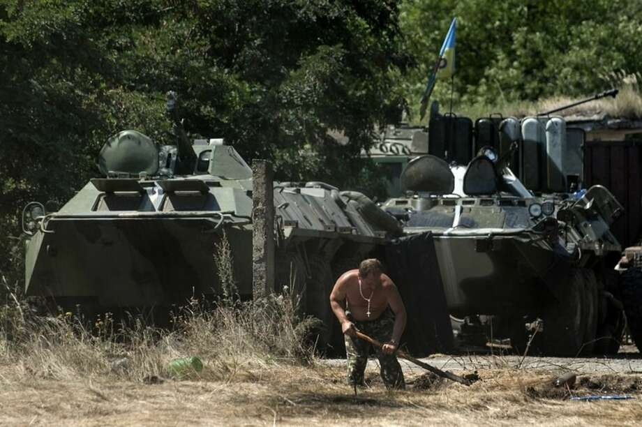 A Ukrainian government soldier sets a position in front of military vehicles in Donetsk region, eastern Ukraine, Saturday, Aug. 9, 2014. A top commander of the pro-Russia insurgency in eastern Ukraine said Saturday that Ukrainian forces have seized a key town, leaving the rebel region's largest city of Donetsk surrounded. (AP Photo/Evgeniy Maloletka)