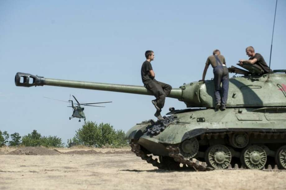 Ukrainian government soldiers sit atop of a tank in Donetsk region, eastern Ukraine, Saturday, Aug. 9, 2014. A top commander of the pro-Russia insurgency in eastern Ukraine said Saturday that Ukrainian forces have seized a key town, leaving the rebel region's largest city of Donetsk surrounded. (AP Photo/Evgeniy Maloletka)