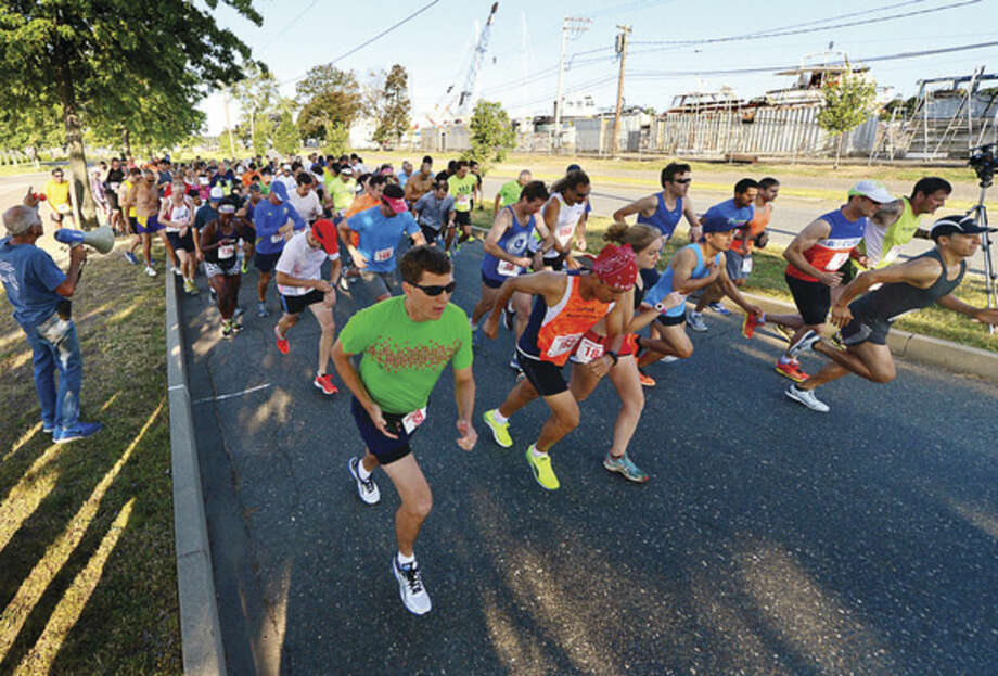 Hour photo / Erik TrautmannRunners head out from the starting line during the Lightfoot Running Club's annual Ian Eaccarino Memorial 9-miler at Calf Pasture Beach on Saturday.