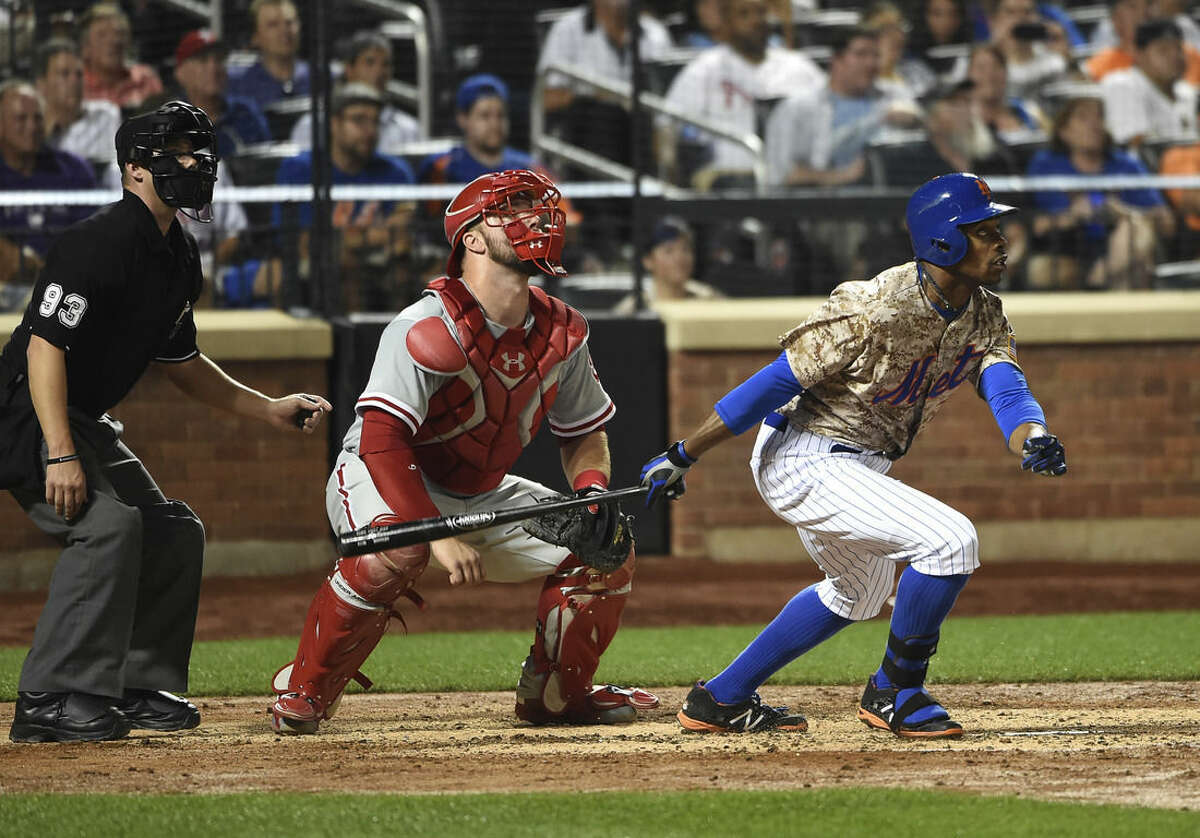 Philadelphia Phillies catcher Cameron Rupp and New York Mets' Curtis Granderson (3) watch Granderson's two-run home run in the fifth inning of a baseball game at Citi Field on Monday, Aug. 31, 2015, in New York. (AP Photo/Kathy Kmonicek)