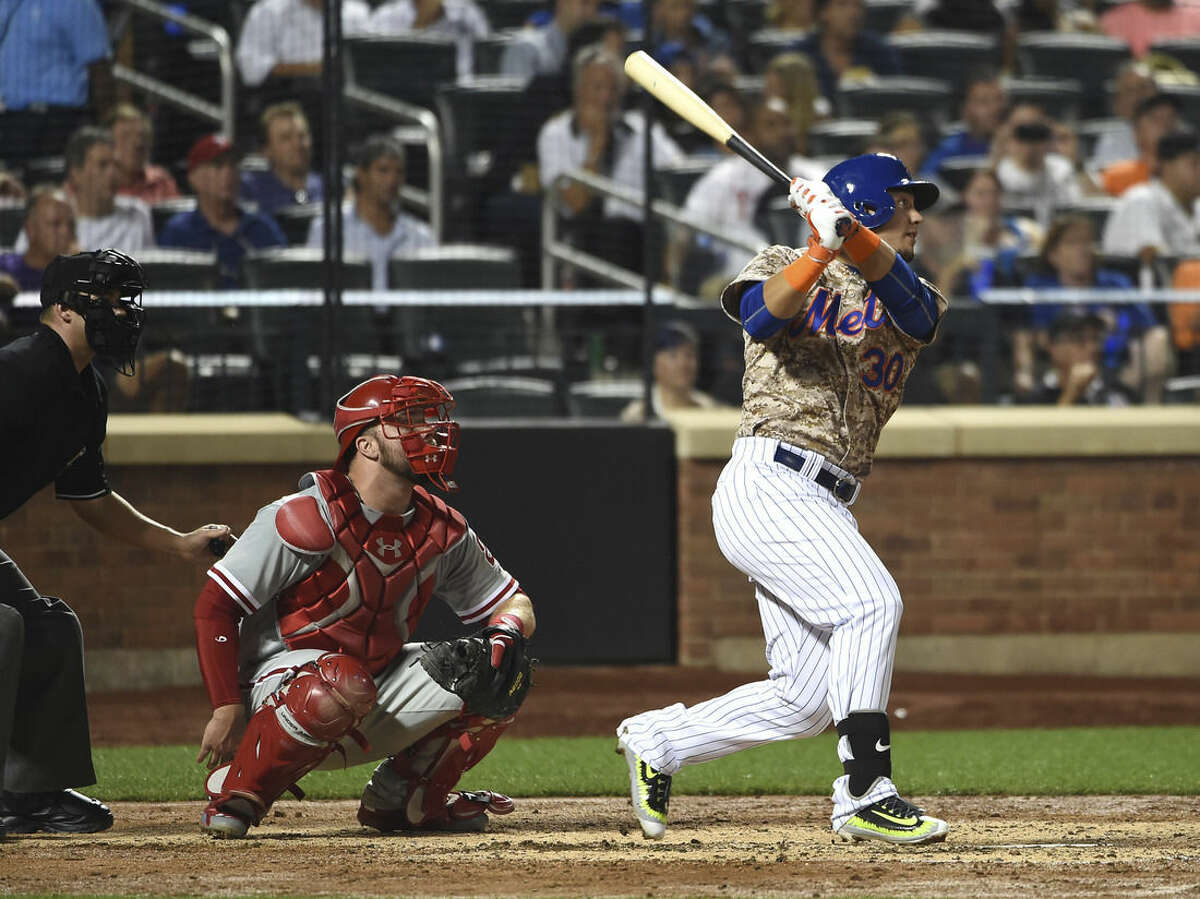 Philadelphia Phillies catcher Cameron Rupp watches New York Mets' Michael Conforto (30) hit a solo home run in the fifth inning of a baseball game at Citi Field on Monday, Aug. 31, 2015, in New York. (AP Photo/Kathy Kmonicek)
