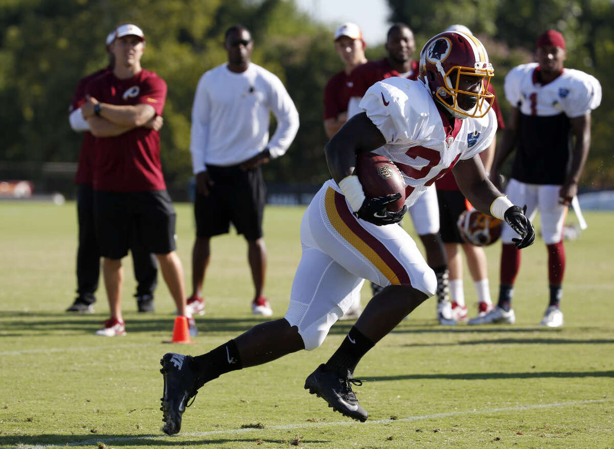 Washington Redskins running back Silas Redd runs with the ball during practice at the team's NFL football training facility, Monday, July 28, 2014 in Richmond, Va. (AP Photo/Alex Brandon)