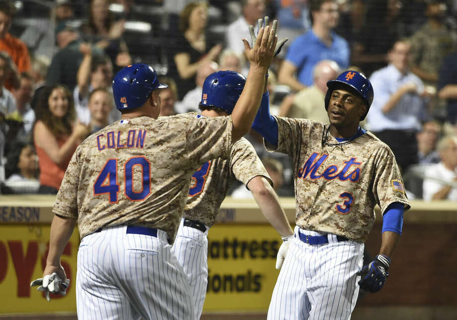 New York Mets' Bartolo Colon (40) and Daniel Murphy (28) greet Curtis Granderson (3) at home plate after Grandson hit a two-run home run off of Philadelphia Phillies starting pitcher Jerad Eickhoff in the fifth inning that also scored Colon in a baseball game at Citi Field on Monday, Aug. 31, 2015, in New York. (AP Photo/Kathy Kmonicek)