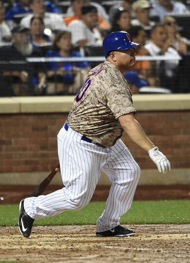 New York Mets' Bartolo Colon follows through for a single off of Philadelphia Phillies starting pitcher Jerad Eickhoff in the fifth inning of a baseball game at Citi Field on Monday, Aug. 31, 2015, in New York. Colon scored on Curtis Granderson's two-run home run. (AP Photo/Kathy Kmonicek)