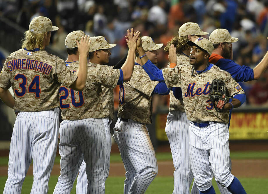 New York Mets' Curtis Granderson (3) celebrates the Mets 3-1 win over the Philadelphia Phillies with teammates at the end of a baseball game at Citi Field on Monday, Aug. 31, 2015, in New York. Granderson hit a two-run home run during the game. (AP Photo/Kathy Kmonicek)