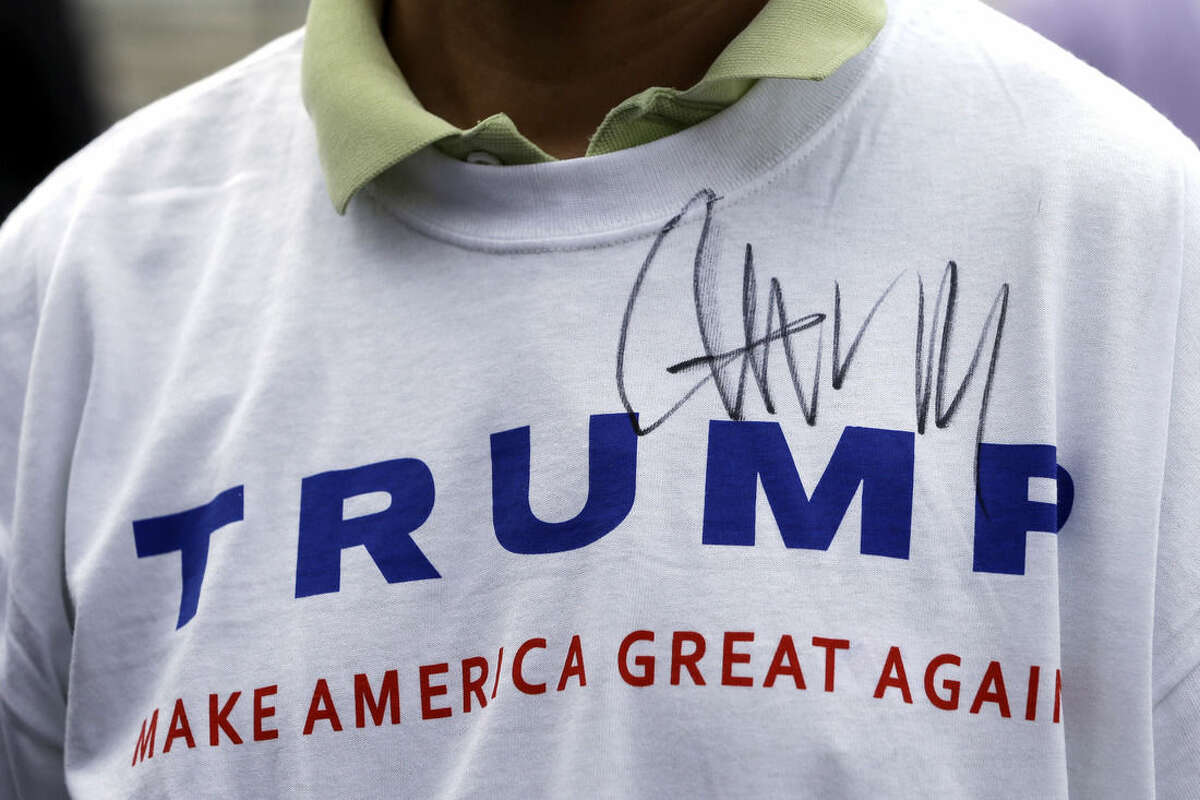 FILE - In this Aug. 29, 2015, file photo, Donald Trump supporter John Wang wears a shirt autographed by the Republican presidential candidate outside the National Federation of Republican Assemblies in Nashville, Tenn. It's been a tumultuous political summer. The unexpected rises of billionaire Donald Trump and socialist Bernie Sanders. When it comes to Trump, Ohio Republicans have a palpable excitement about his brash brand of politics, and a deep uncertainty about his qualifications to serve as president. (AP Photo/Mark Humphrey, File)