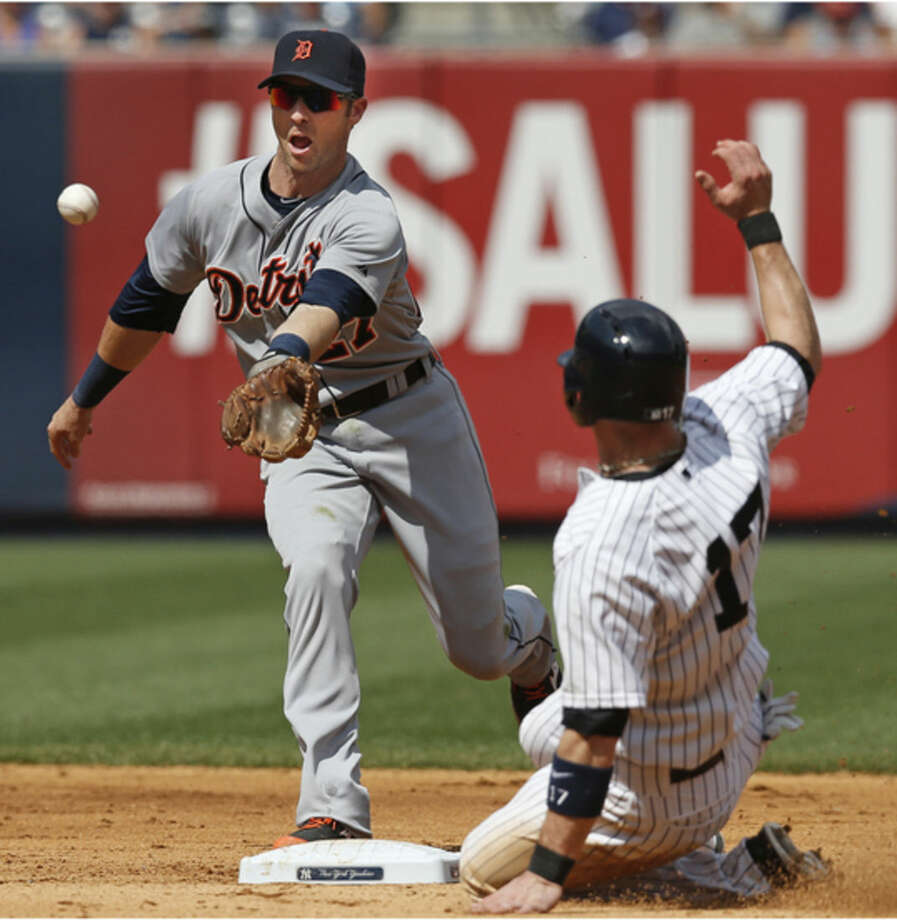Detroit Tigers shortstop Andrew Romine reacts as he fields Brett Gardner's seventh-inning ground ball single that bounced in the infield, loading the bases, as New York Yankees Brendan Ryan slides into second in a baseball game at Yankee Stadium in New York, Thursday, Aug. 7, 2014. (AP Photo/Kathy Willens)
