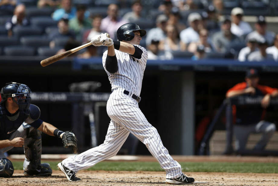 New York Yankees' Stephen Drew hits a fourth-inning, ground-rule, RBI double off Detroit Tigers starting pitcher Rick Porcello, scoring the Yankees' Carlos Beltran, in a baseball game at Yankee Stadium in New York, Thursday, Aug. 7, 2014. (AP Photo/Kathy Willens)
