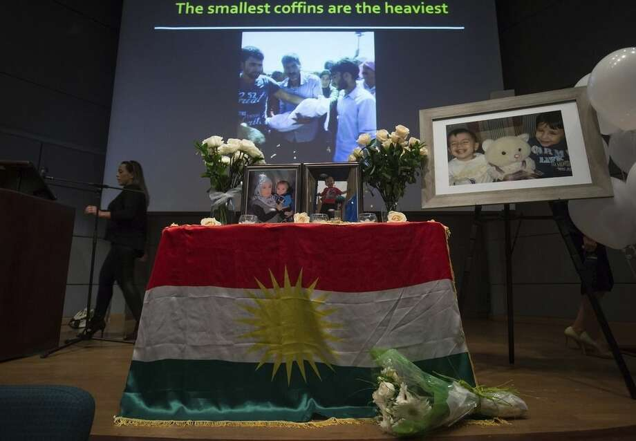 Photographs of late Syrian brothers Alan and Ghalib Kurdi and their mother, Rehanna, are displayed as Hoba Said, left, prepares for their memorial service in Vancouver, British Columbia, Canada on Saturday, Sept. 5, 2015. The body of 3-year-old Alan was found on a Turkish beach after the small rubber boat he, his 5-year-old brother, Ghalib and their mother, Rehanna, were in capsized during a voyage from Turkey to Greece. (Darryl Dyck/The Canadian Press via AP) MANDATORY CREDIT