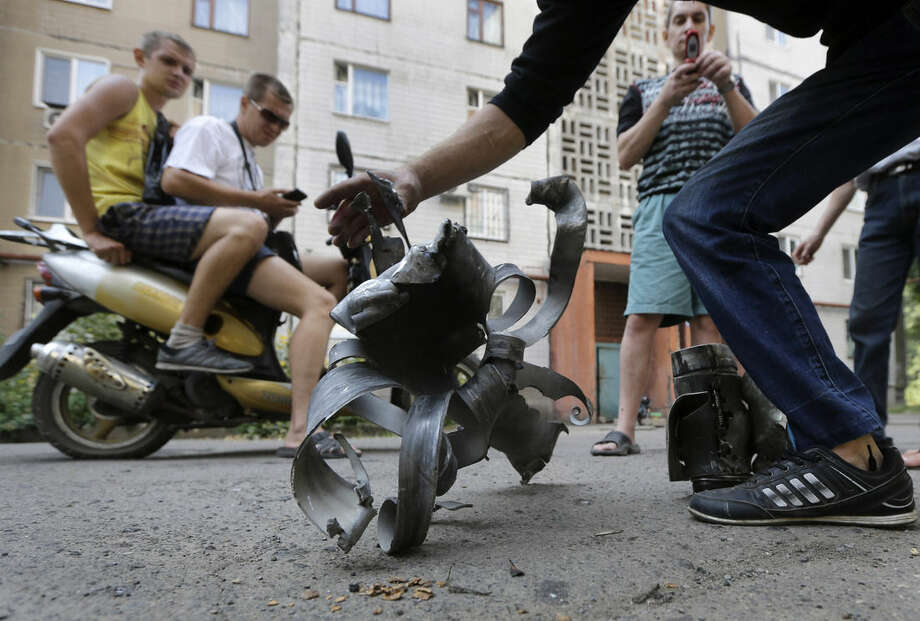 Local residents display fragments of a shell in Donetsk, eastern Ukraine, Friday, Aug. 8, 2014. At least three civilians have been killed and another 10 wounded in overnight shelling of the main rebel stronghold in eastern Ukraine besieged by government forces, officials said. (AP Photo/Sergei Grits)