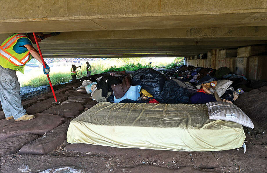 Hour photo / Erik Trautmann Norwalk Department of Public Works employees and Norwalk police remove a homeless encampment from underneath the Stafolino Bridge Wednesday.