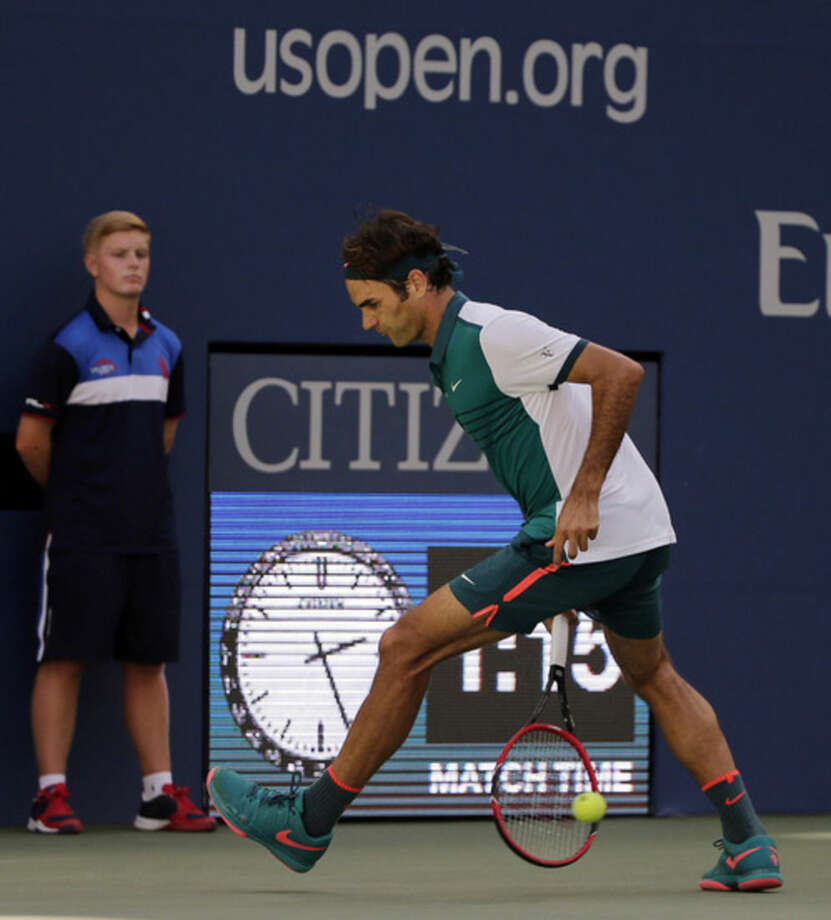 Roger Federer, of Switzerland, returns a shot from between his legs to Philipp Kohlschreiber, of Germany, during the third round of the U.S. Open tennis tournament, Saturday, Sept. 5, 2015, in New York. (AP Photo/Charles Krupa)