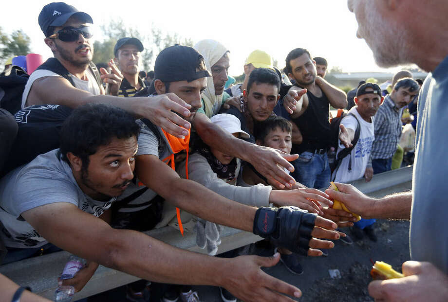 Migrants reach out for food during their walk out of Budapest, Hungary, Friday, Sept. 4, 2015. Over 150,000 people seeking to enter Europe have reached Hungary this year, most coming through the southern border with Serbia, and many apply for asylum but quickly try to leave for richer EU countries. (AP Photo/Frank Augstein)