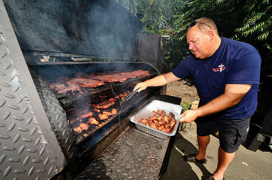 Hour photo / Erik Trautmann Paramedic Andy Dinitz cooks up chicken wings and other barbeque for the Westport EMS team during the 8th annual Blues, Views and BBQ Festival at Westport's Levitt Pavilion Saturday.
