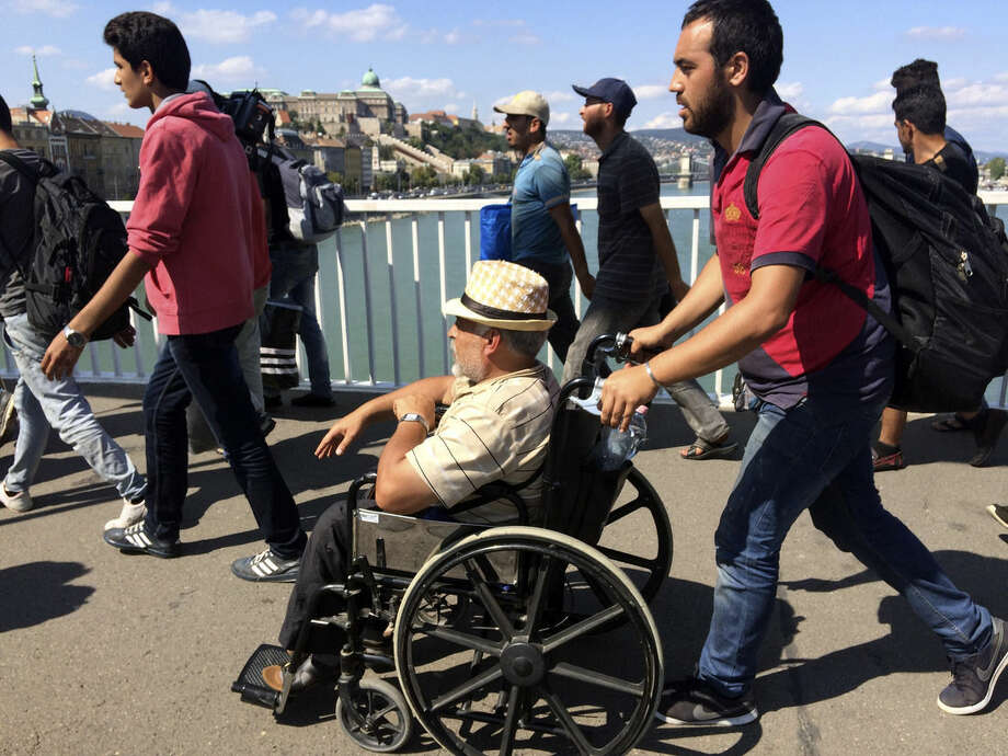 A man in a wheelchair in a group of hundreds of migrants crosses the river Danube in Budapest, Friday Sept, 4, 2015, after they decided to walk toward Austria. Thousands have been camped out at Budapest's Keleti train station for days, before they decided to try and reach their destination on foot. (AP Photo/Bela Szandelszky)