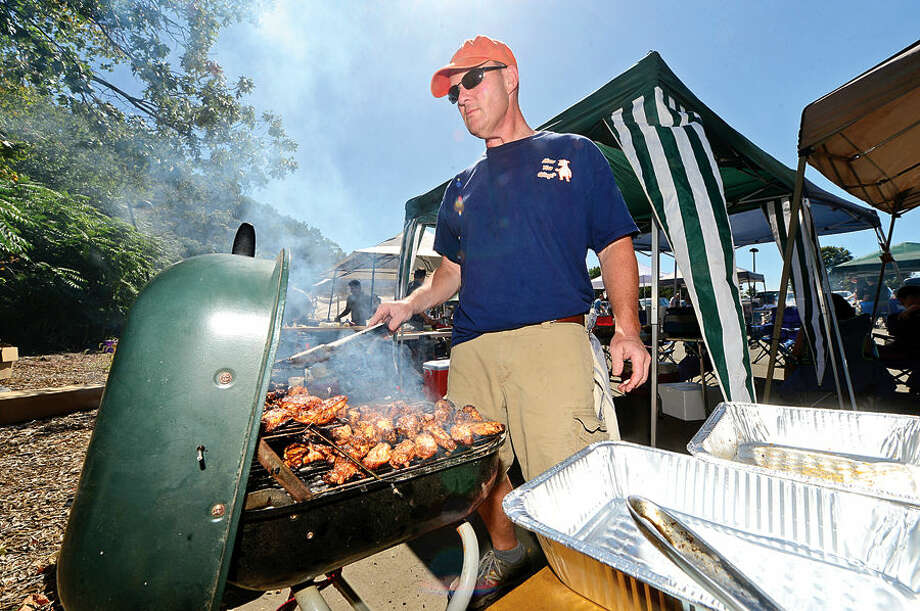 Hour photo / Erik Trautmann Dan Kowalewski of the How You Q'ing team cooks up some chicken wings during the 8th annual Blues, Views and BBQ Festival at Westport's Levitt Pavilion Saturday.