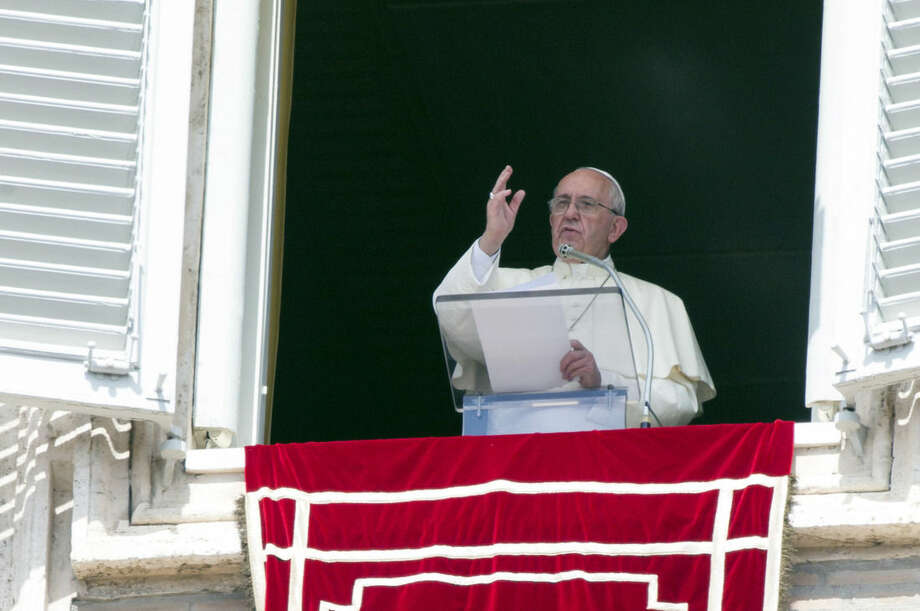 """Pope Francis delivers his blessing to faithful during the Angelus noon prayer from his studio window overlooking St. Peter's Square at the Vatican, Sunday, Sept. 6, 2015. The Vatican will shelter two families of refugees """"who are fleeing death"""" from war or hunger, Pope Francis announced Sunday as he called on Catholic parishes, convents and monasteries across Europe to do the same. (AP Photo/Riccardo De Luca)"""