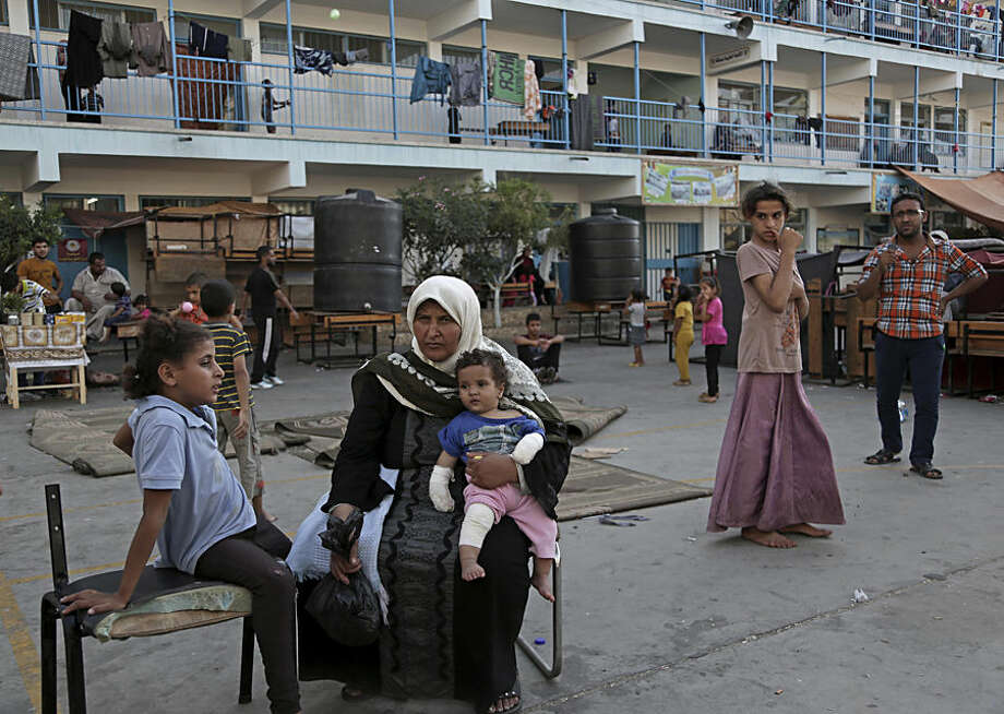 Displaced Palestinian woman Reda Salaman, 46, foreground, holds her wounded grandson Omar, 11 months, in the yard of the U.N. school where they sought refuge during the war, in Beit Lahiya, in the northern Gaza Strip, Tuesday, Aug. 12, 2014. Tens of thousands of Palestinians have been displaced in the Israel-Hamas war that began July 8, at least 10,000 housing units have been destroyed and many have found refuge at U.N. schools turned into shelters. (AP Photo/Adel Hana)
