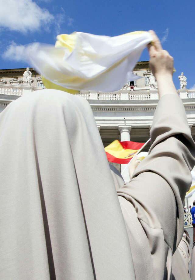 "Nuns wave to Pope Francis, background top, during the Angelus noon prayer he delivered from his studio window overlooking St. Peter's Square at the Vatican, Sunday, Sept. 6, 2015. The Vatican will shelter two families of refugees ""who are fleeing death"" from war or hunger, Pope Francis announced Sunday as he called on Catholic parishes, convents and monasteries across Europe to do the same. (AP Photo/Riccardo De Luca)"