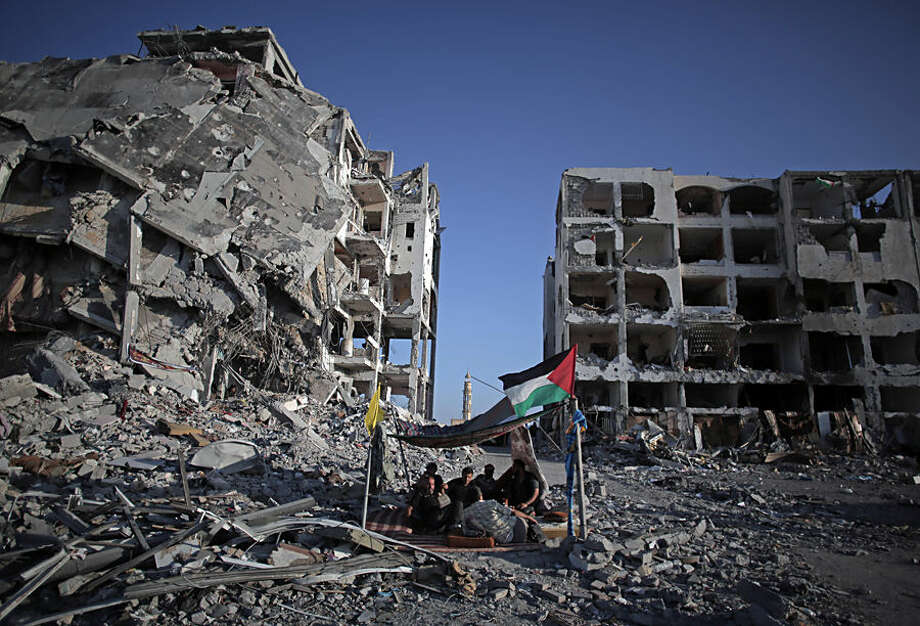 Palestinian Ziad Rizk, 38, sits with others in a shelter made of a blanket stretched over four boles next to one of the destroyed Nada Towers, where he lost his apartment and clothes shop, in the town of Beit Lahiya, northern Gaza Strip, Monday, Aug. 11, 2014. (AP Photo/Khalil Hamra)
