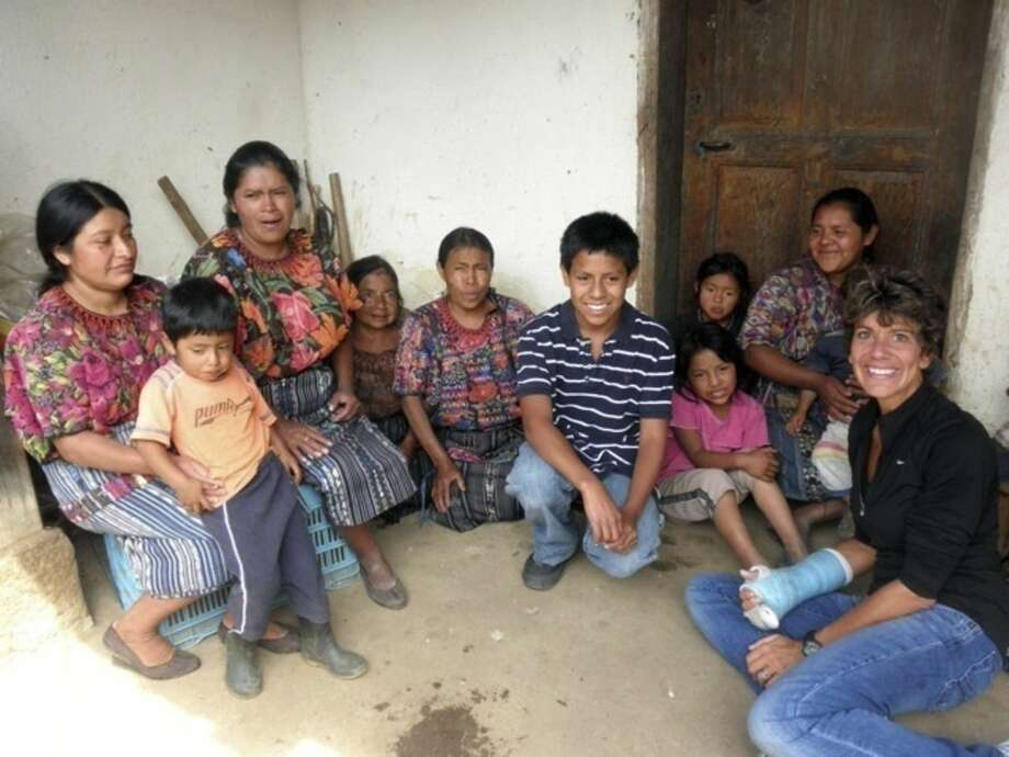 In this July 2012 photo provided by the family, Jake Niergarth, 14, center with striped shirt, and his adoptive mother, Lisa, right, pose for a photo with residents of a rural area outside of Chichicastenango, Guatemala. When the Niergarths adopted Jake through a major U.S. adoption agency in 1999, they learned his birth mother's name, but little else about her or why she relinquished Jake. (Steve Niergarth via AP)