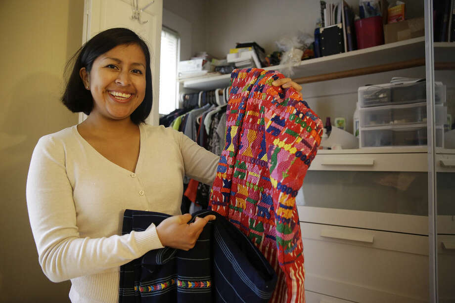 In this Tuesday, July 14, 2015 photo, Gemma Givens, 25, holds up a huipil shirt and corte, that were given to her by her family in Guatemala, at her apartment in Berkeley, Calif. Givens, an adoptee who works at UC Berkeley, has been trying to create a Facebook community for fellow Guatemalan adoptees. In the United States, there are more than 29,000 young people born in Guatemala and adopted by U.S. families. (AP Photo/Eric Risberg)