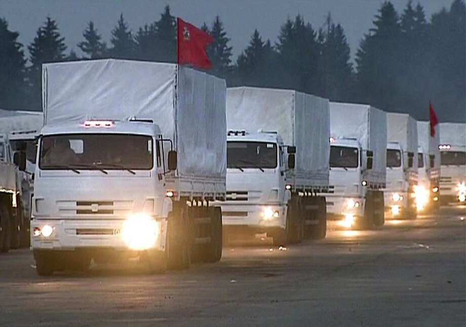 In this image taken from video a convoy of white trucks with humanitarian aid leaves Alabino, outside Moscow Tuesday, Aug. 12, 2014. The convoy of 280 Russian trucks headed for eastern Ukraine early Tuesday, one day after agreement was reached on an international humanitarian relief mission. But the international Red Cross, which is due to coordinate the operation, said it had no information on what the trucks were carrying or where they were going. (AP Photo/ RTR via Associated Press Television) TV OUT RUSSIA OUT