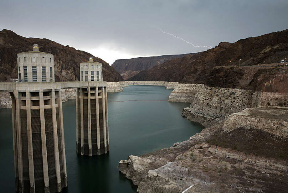 In this July 28, 2014 photo, lightning strikes over Lake Mead near Hoover Dam at the Lake Mead National Recreation Area in Arizona. On the left are the Arizona intake towers of Hoover Dam. The bathtub ring of light minerals shows the high water mark of the reservoir which has shrunk to its lowest point since it was first filled in the 1930s. (AP Photo/John Locher)