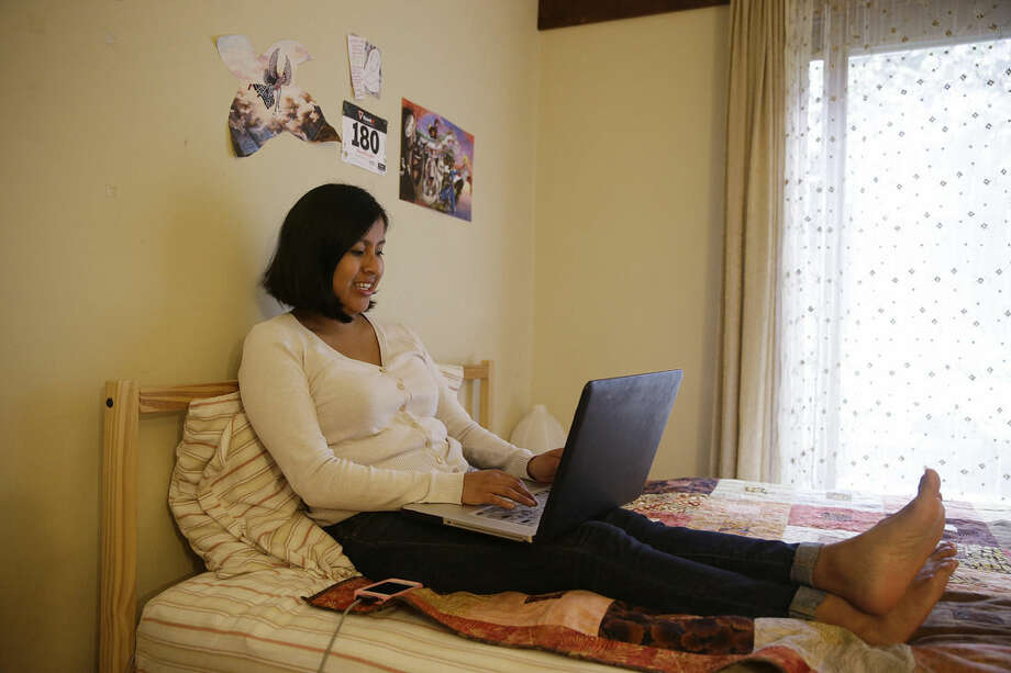 In this Tuesday, July 14, 2015 photo, Gemma Givens, 25, works on her laptop computer at her apartment in Berkeley, Calif. Givens, an adoptee who works at UC Berkeley, has been trying to create a Facebook community for fellow Guatemalan adoptees. (AP Photo/Eric Risberg)