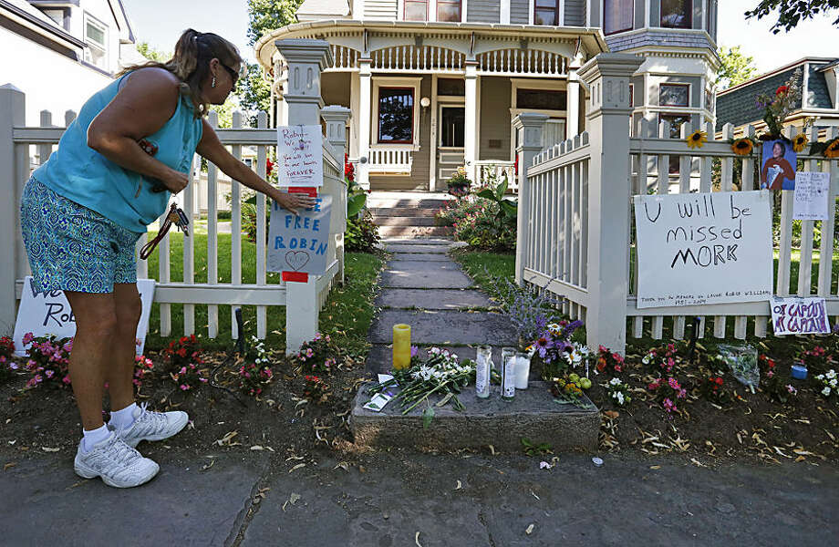 "Boulder resident Wendy Darling tapes up a sign that reads ""Fly Be Free Robin,"" as she pays tribute to Robin Williams at a makeshift memorial outside the home where the 80s TV series ""Mork & Mindy,"" was set, in Boulder, Colo., Tuesday Aug. 12, 2014. Williams, the Academy Award winner and comic supernova whose explosions of pop culture riffs and impressions dazzled audiences for decades and made him a gleamy-eyed laureate for the Information Age, died Monday in an apparent suicide. He was 63. (AP Photo/Brennan Linsley)"