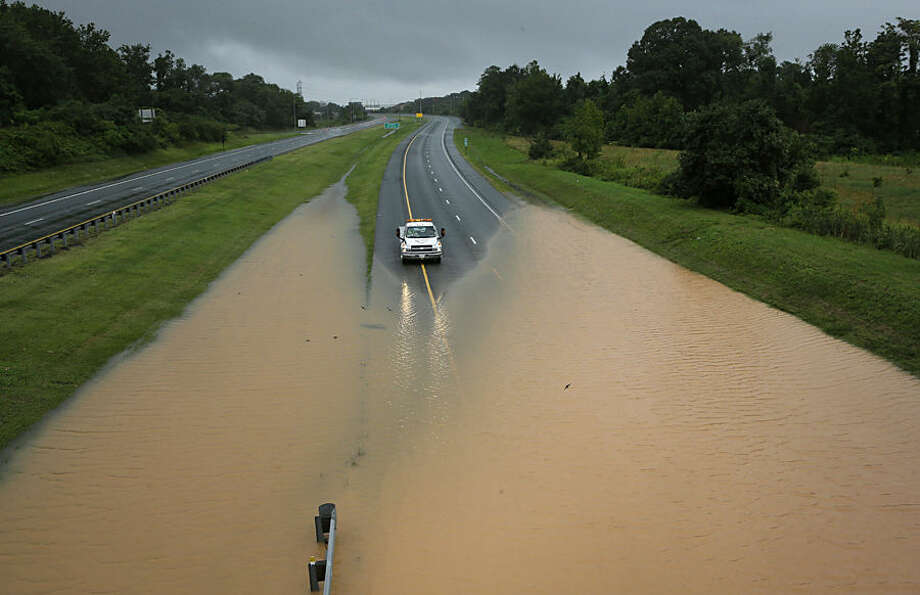 A truck sits at the edge of a flooded section of Interstate 695 in Baltimore, Tuesday, Aug. 12, 2014, after heavy rains fell across the Mid-Atlantic region. Officials shut down the Baltimore beltway in both directions at Quarantine Road due to heavy flooding. (AP Photo/Patrick Semansky)