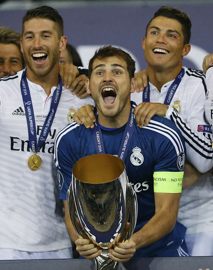 Real Madrid's goalkeeper Iker Casillas, centre, lifts the trophy with Sergio Ramos, left and Cristiano Ronaldo after beating Sevilla 2-0 during the UEFA Super Cup soccer match between Read Madrid and Sevilla at Cardiff City Stadium in Wales Tuesday, Aug. 12, 2014. AP Photo/Kirsty Wigglesworth)