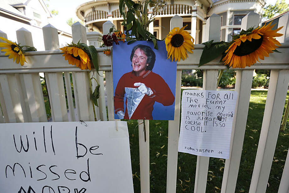 A photo of the late actor Robin Williams playing Mork from Ork hangs with flowers and notes left by people paying their respects, at a makeshift memorial in Boulder, Colo., Tuesday Aug. 12, 2014, outside the home where the 80s TV series Mork & Mindy, starring Williams, was set. Williams, the Academy Award winner and comic supernova whose explosions of pop culture riffs and impressions dazzled audiences for decades and made him a gleamy-eyed laureate for the Information Age, died Monday, Aug. 11, in an apparent suicide. He was 63. (AP Photo/Brennan Linsley)
