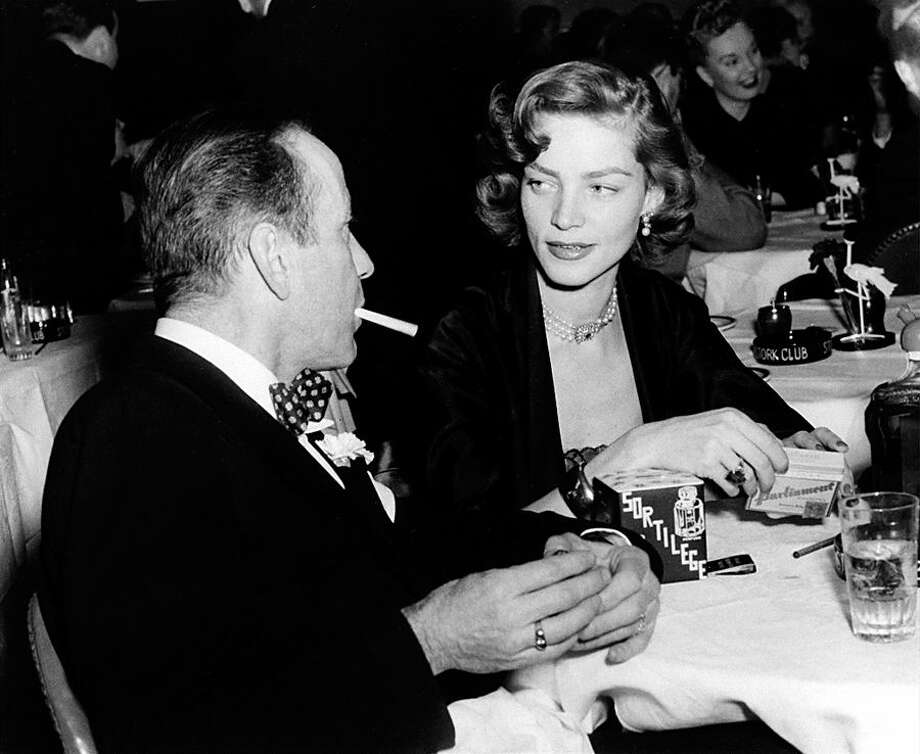 FILE - In this Feb. 1950 file photo actor Humphrey Bogart, left, and his wife, actress Lauren Bacall, appear at the Stork Club in New York. Bacall, the sultry-voiced actress and Humphrey Bogart's partner off and on the screen, died Tuesday, Aug. 12, 2014 in New York. She was 89. (AP Photo, File)