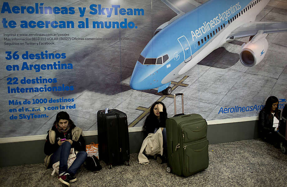Stranded passengers wait inside the metropolitan airport, in Buenos Aires, Argentina, Tuesday, Aug. 12, 2014. Thousands of passengers remained grounded at the two Buenos Aires' airports Tuesday due to an Aerolineas Argentinas and Austral's pilots strike. The pilots are demanding a wage increase. (AP Photo/Natacha Pisarenko)