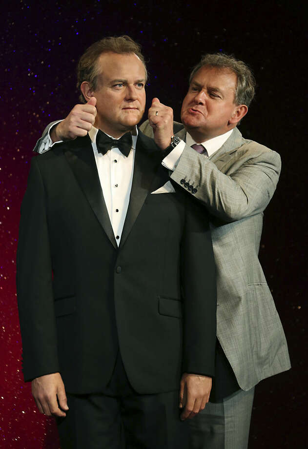 British actor Hugh Bonneville, right, who plays Downton Abbey's Lord Grantham, attempts to pull the cheeks of his wax figure at Madame Tussauds in central London, Tuesday, Aug. 12, 2014. (Photo by Joel Ryan/Invision/AP)