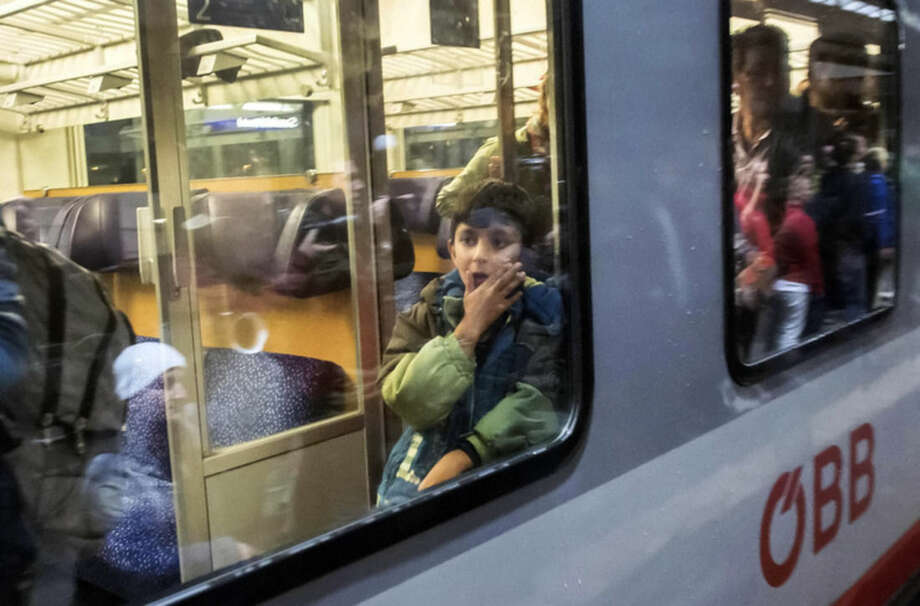 A young boy arrives in a train of the Austrian railway at the train station in Saalfeld, central Germany, Saturday, Sept. 5, 2015. Hundreds of refugees arrived in a train from Munich to be transported by busses to an accomodation centre. (AP Photo/Jens Meyer)