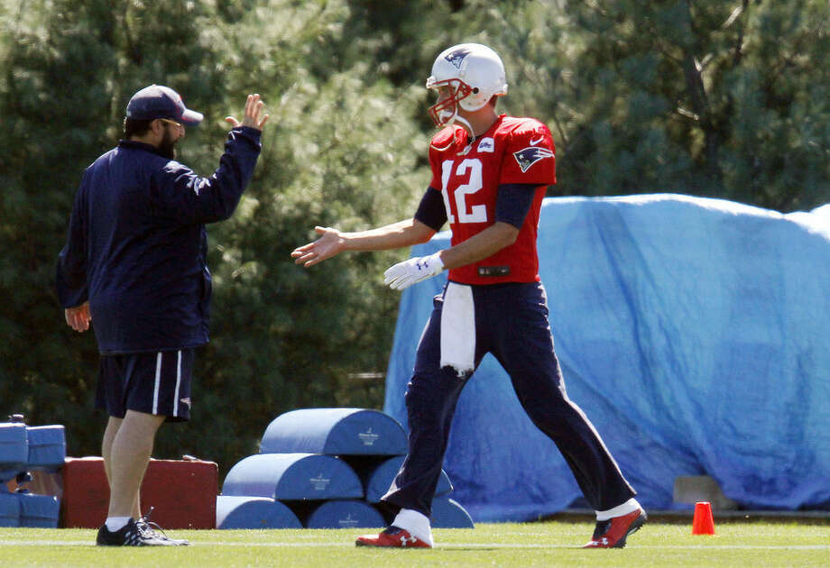 New England Patriots football quarterback Tom Brady (12) greets New England Patriots defensive coordinator Matt Patricia, left, at the start of practice Saturday, Sept. 5, 2015, in Foxborough, Mass. A federal judge overturned Brady's four-game suspension last Thursday. The Patriots host the Pittsburgh Steelers to open the NFL season Thursday night. (AP Photo/Bill Sikes)