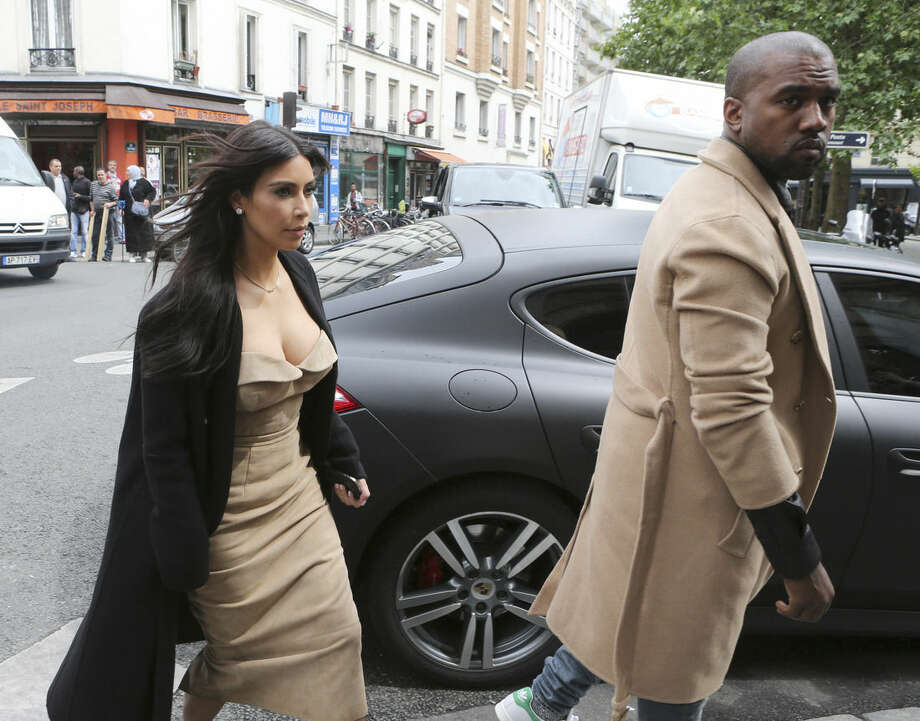FILE - Kim Kardashian and U.S rap singer Kanye West arrive at a luxury shop in Paris, Wednesday, May 21, 2014 file photo. Recently, Kardashian West spoke about baby North, the success of her online game, her upcoming book of selfies and how motherhood has emboldened her. (AP Photo/Jacques Brinon, File)