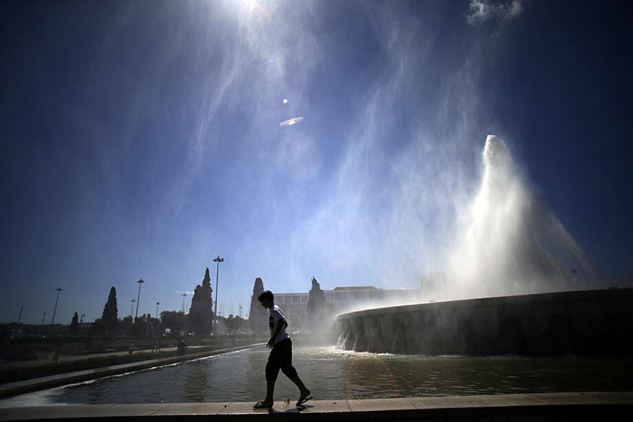 A youngster cools off with the water spread by the wind in a public fountain at Lisbon's Belem neighbourhood, Tuesday, Aug. 12, 2014. On summertime Belem is an area very frequented by tourists that visit the capital iconic monuments such as the Belem Tower, the Jeronimos monastery and the Padrao dos Descobrimentos, a 1960's monument to the Portuguese discoveries. (AP Photo/Francisco Seco)
