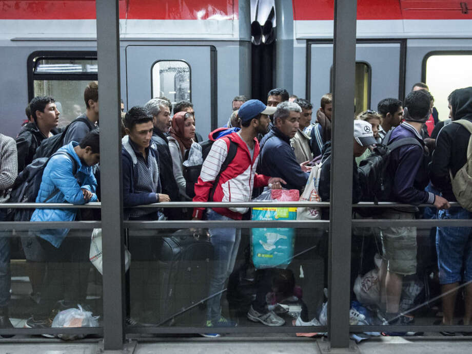 Refugees arrive at the train station in Saalfeld, central Germany, Saturday, Sept. 5, 2015. Hundreds of refugees arrived in a train from Munich to be transported by busses to an accomodation centre. (AP Photo/Jens Meyer)