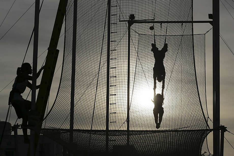 In this photo taken Sunday, Aug. 10, 2014, flying trapeze instructor and school owner William Hsu swings with his student during their first day of practice at the Flying Trapeze Philippines School in suburban Makati, south of Manila, Philippines. The outdoor school sits in a grassy clearing surrounded by high-rises in the business district in metropolitan Manila. Chinese American businessman Hsu said he opened the facility more than a week ago to build self-confidence and promote health among students. The sport has been gaining adherents, he said, with more than 150 such schools worldwide. (AP Photo/Aaron Favila)