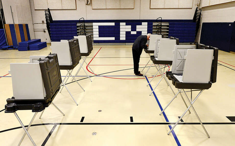 Hour photo / Erik Trautmann Ron Parris fills out his ballot during primary voting Tuesday at Cider Mill School in Wilton.