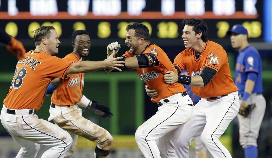 Miami Marlins' Martin Prado, second from right, is congratulated by teammates after hitting a baseball game-winning sacrifice fly with the bases loaded against the New York Mets in the ninth inning Sunday, Sept. 6, 2015, in Miami. Marlins' J.T. Realmuto scored the game-winning run in the 4-3 victory. (AP Photo/Alan Diaz)