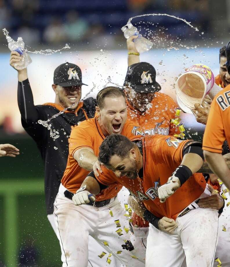 Miami Marlins' Martin Prado, foreground, is doused by teammates after hitting a baseball game-winning sacrifice fly with the bases loaded against the New York Mets in the ninth inning Sunday, Sept. 6, 2015, in Miami. Marlins' J.T. Realmuto scored the game-winning run in the 4-3 victory. (AP Photo/Alan Diaz)