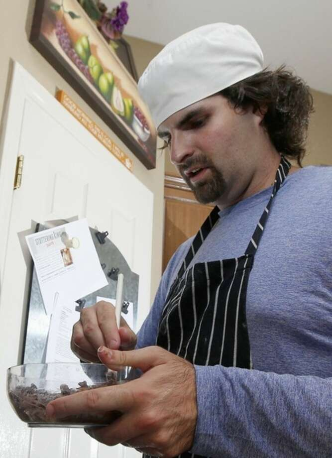 In this July 15, 2014 photo, Matt Cottle, owner of Stuttering King Bakery, works on a bowl of chocolate chips in his parents' kitchen in Scottsdale, Ariz. Cottle is one of a few known small business owners with autism, a brain disorder that affects a person's ability to comprehend, communicate and interact socially. (AP Photo/Ross D. Franklin)