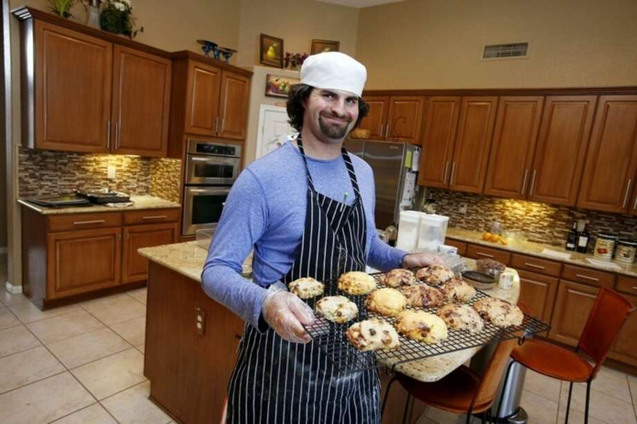 In this July 15, 2014 photo, Matt Cottle, owner of Stuttering King Bakery, smiles as he holds a tray of his scones in his parents' kitchen in Scottsdale, Ariz. Cottle is one of a few known small business owners with autism, a brain disorder that affects a person's ability to comprehend, communicate and interact socially. (AP Photo/Ross D. Franklin)